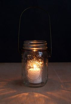The easiest & super charming DIY hanging mason jar lights using up-cycled glass bottles and dry cleaners wire hangers. Detailed step by step tutorial! - A Piece of Rainbow Mason Jar Hanger, Mason Jar Art, Mason Jar Gifts, Mason Jar Candles, Hanging Mason Jar Lights, Mason Jar Lighting, Diy Hanging, Mason Jar Projects, Jar Lanterns