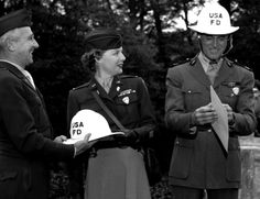 """Heidelberg, Germany, October 4, 1948: Heidelberg Post fire marshal Ernie J. Albertson presents Ann Sheridan and Cary Grant with orders —and suitable headgear — recognizing them as honorary fire chiefs of the post. The ceremony was part of Heidelberg's Fire Prevention Week drive. The two movie stars were in Germany for the filming of Howard Hawks' comedy, """"I Was a Male War Bride,"""" in which Grant plays a French captain who falls in love with American lieutenant Sheridan."""