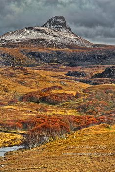 An autumn storm gathers behind Stac Pollaidh, a mountain in the Northwest Highlands of Scotland. The peak displays a rocky crest of Torridonian sandstone, with many pinnacles and steep gullies