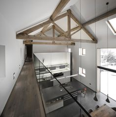 This would be an option when considering removing an upper floor - replace with a balcony overlooking a central kitchen/dining area and have an upper floor room located at one end of the building. This provides a dramatic design feature, awash with light and space. Good use of artificial lights; along the balcony, kitchen and pendant lights hanging from the ceiling.