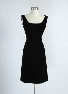 """Early 1960's Oleg Cassini black rayon velvet cocktail dress with straps that are almost off-the-shoulder. Very flattering along the bust. Velvet is silky and plush. Metal zipper up the back. Label reads, """"Young America by Oleg Cassini."""""""