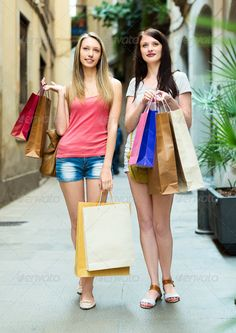 Two smiling girls walking with purchases ...  20-30, american, bags, buying, casual, caucasian, city, cloth, clothing, consumerism, couple, customer, discount, european, fashion, female, friends, girls, happy, holding, leisure, lifestyle, long-haired, ordinary, outdoor, passion, people, person, positive, purchases, sales, satisfaction, shopaholic, shopper, shopping, shorts, smiling, souvenirs, street, tour, tourists, town, travel, two, vacation, weekend, white, women, young