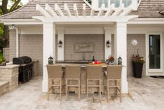 Outdoor bar - kitchen area is complete with a barbecue, sink and refrigerator. The beautiful natural stone patio brings it all together. #outdoorkitchen #pergola #outdoors Southview Design