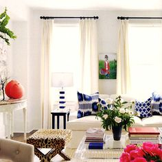 Claiborne Swanson Frank: Madeline Weinrib blue ikat pillows + neutral Stark rug + light gray walls + lucite coffee table + pink flowers + X-bench + pop of orange + blue and white LAMP! Amazeballs