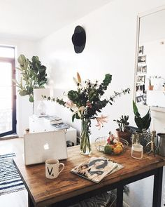 Beautiful wooden desk with a flower bouquet, a laptop and an cozy atmosphere.