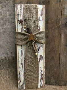 This piece is made from repurposed, distressed trim. Cross is made with burlap and a rusty star and berry trim. Measures approx 5 1/2 wide by 16 1/2 tall.
