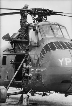 January 01, 1965 License American soldiers, gunner Marine Pfc Wayne Hoilien (top) and Corporal James C Farley (of Yankee Papa 13) inspect their helicoptor before a mission, Da Nang, Vietnam, 1965.Less