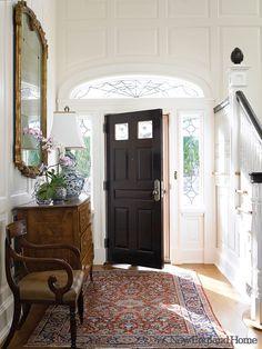 Entryway, wainscoting, black handrail, black door, persian rug...