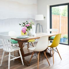 Dining area with cute wall mural, wood dining table and different style chairs