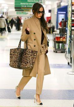 Fashion-Looks: Im edlen, karamellfarbenen Wollmantel und passender Hose ist Victoria Beckham am New Yorker Flughafen unterwegs. Spannend wird der Look aber erst richtig durch ihre Leo-Print-Tasche.