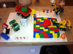 My sons Lego cake- the Lego construction crew is building his cake. Got white fondant. And the primary colors of Wilton fondant. The primary colors we rolled them out and pressed a Lego plate in it to get the Lego imprint. After about 4 hours and a couple glasses of wine hubby and I finished the cake!! And my little guy loved it!!!
