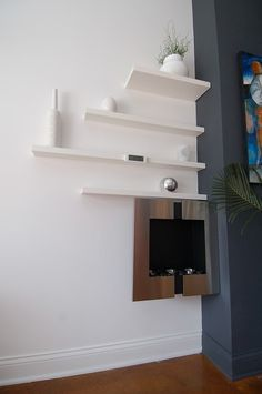 White floating shelves with minimal white decor.