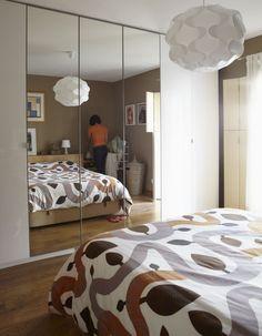 petite chambre à coucher aménagée avec une armoire encastrée avec porte miroir