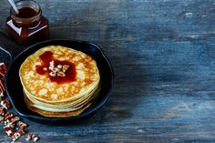 #Pancakes in pan  Homemade american pancakes with pecans and chocolate caramel sauce on vintage cast-iron frying pan over rustic background selective focus. Delicious dessert for breakfast
