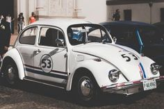 Hirby car near blue car White Volkswagen Herbie Beetle on the street Iphone Wallpaper Bible, Watercolor Wallpaper Iphone, Hd Wallpaper, Volkswagen New Beetle, Beetle Car, Vw, Film Cars, Movie Cars, Automobile