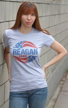 Ronald Reagan's 1980 Presidential campaign used a number of different graphic styles on buttons and other materials, including swirled flag design, which originated on buttons. We print the design on a thin, heather gray t-shirt, available in unisex and a woman's style. $19.99