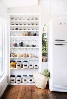 Glass jars on shelves, beautiful rustic wooden floor and dreamy kitchen. This shows the perfect way to organise ingredients in a beautiful way!