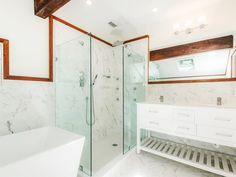 Crisp marble and white bathroom with glass shower // Angelina Jolie's childhood home