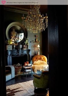 elegant neoclassic living room with black walls, an antique fireplace and a gold chandelier