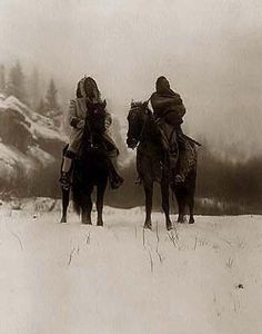 You are looking at a beautiful picture of Indians in Winter. It was created in 1908 by Edward S. Curtis.    The picture presents Two Crow (Apsaroke) Indian men. One is wearing a hooded coat, ant the other is wrapped in an Indian blanket. Both are on horseback. The ground is covered with snow, and trees and hillside are seen in the background.    We have created this collection of illustrations primarily to serve as a valuable educational tool. Contact curator@old-picture.com.