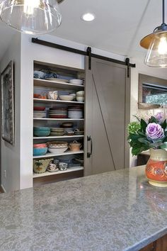 Barn door pantry offers plenty of storage space for chinaware [Design: Robert Paige Cabinetry / Photography by William Quarles]