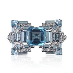Exceptional Art Decó aquamarine and diamond stylised buckle brooch, set to the centre with a cut-cornered rectangular aquamarine flanked by stepped and baguette-cut aquamarine four-stone shouders to brilliant-and baguette-cut diamond mount, set to the four corners with a wedge shaped aquamarine embelllished by further baguette and square-cut aquamarines, signed by Cartier London.