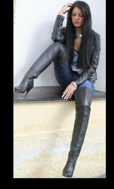 Brunette in leather jacket jeans and black thigh boots