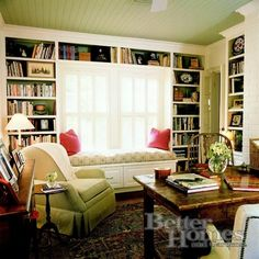 Cozy library with window seat, wing chairs and built in shelving. I like the addition of the table for use as a low key, stylish home office as well.