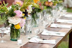 Strong wood tables with burlap runner, lanterns, & Ball jar filled mixed florals Photograph by Diana Deaver Weddings http://www.storyboardwedding.com/an-intimate-rustic-private-home-wedding-with-a-french-feel-window-pane-guest-book/