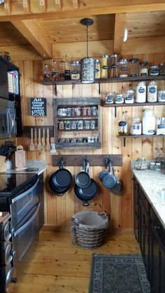 Simple rustic cabin kitchen - lots of open shelves against a wood wall.