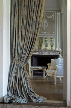 #Drapery with puddle.  Traditional Style Blue damask silk with trim drapery panel.  Classical Room.  Whitewashed floors. European Home Style.  The drape reminds me of a ball gown.   I love the idea of thick drapery as a room divider