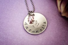 Celebrate your little one with this personalized hand stamped necklace! Stamped on a 1 inch stainless steel disc and adorned with a pearl or Swarovski crystal of your choice, this necklace makes a great gift for your favorite mom or mom-to-be. Pictured with a hand print stamped in the center, other design stamps are also available, including hearts, a teddy bear, foot prints, and more! $19.50