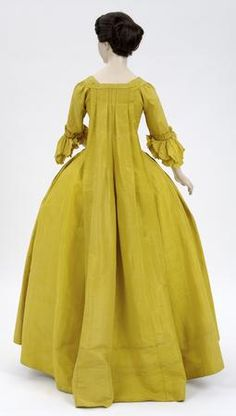 Silk sack-back gown or robe à la Française with silk taffeta petticoat (back view), 1760s. The vibrant color, sometimes called Chinese yellow, was probably dyed with weld, a natural plant dye. It was a particularly fashionable color for dresses in Britain during the 1760s. Dress is thought to have belonged to Mrs John Richardson, the wife of a wealthy fishmonger. Mr Richardson purchased a country estate in Pitfour, Perthshire, 1780 and commissioned Robert Adam to build Pitfour castle.  © CSG…
