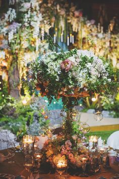 Lush wedding table decor with flowers, vines and candles // A Midsummer Night's Dream-Inspired Wedding with Two Paolo Sebastian Dresses {Facebook and Instagram: The Wedding Scoop}