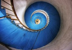 Beautiful blue spiral staircase in tower with grey walls