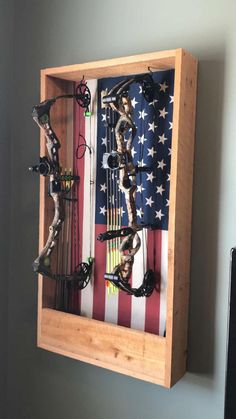 Bow holder - use wood panel wall paper for the back instead of flag Bow Rack, Bow Hanger, Archery Shop, Archery Hunting, Hunting Gear, Archery Range, Archery Bows, Hunting Bows, Hunting Stuff