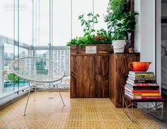 Executado pela Marcenaria Simão, o móvel de pinho tingido de extrato de nogueira com suporte para horta esconde, embaixo, a caixa de ventilação do ar-condicionado. Projeto de Marcela Madureira.