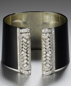 A fine and rare Art Deco black lacquer and diamond cuff bangle, by Cartier, circa 1934. The wide, slightly tapering, black lacquer sprung cuff, with pierced geometric terminals of brilliant, single, square and baguette-cut diamonds, mounted in gold and platinum, diamond terminals detach to be worn as dress clips, signed Cartier London, numbered.  (=)