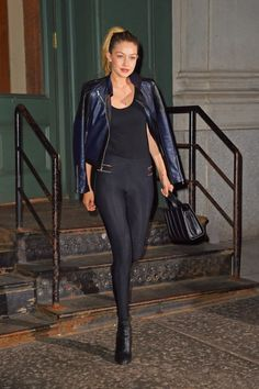 Gigi Hadid wears a black leather jacket over a black tank and leggings, pairing the look with black booties.