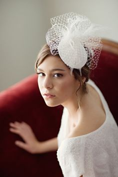 Bridal hat made from a silk dupioni wrapped buckram hat base, Russian veiling, goose, ostrich, and rooster feathers.
