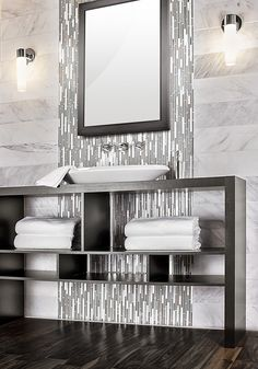 Stacked statuario wall tile with glass and stone accent waterfall behind mirror. Dramatic dark hardwood floor with open vanity.