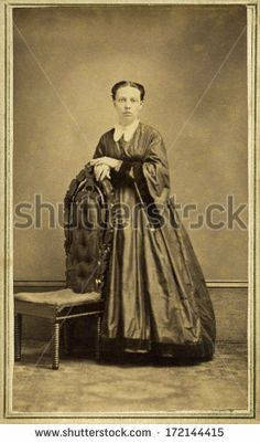 CIRCA 1865 A vintage Cartes de visite photo of young pioneer woman standing chair. She is dressed in hoop skirt dress with pagoda sleeves. A photo from the Civil War era. A digital copy of this photo can be purchased at the above web link.