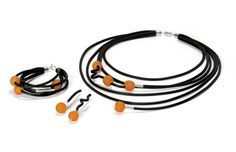 Splash of Color Jewelry by Dagmara Costello. Vibrant orange African trading glass beads and sterling silver accents add a splash of color to asymmetrical pieces created from black rubber tubing. Five-strand necklace has magnetic clasp. Fall Jewelry, Amber Jewelry, Jewelry Art, Jewelry Ideas, Wire Earrings, Unique Earrings, Polymer Clay Earrings, Stone Necklace, Stone Jewelry