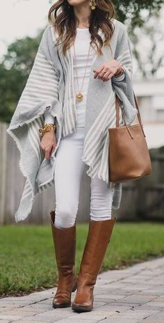 Woman wearing white jeans, white top, gray and white poncho, brown leather handbag and brown boots