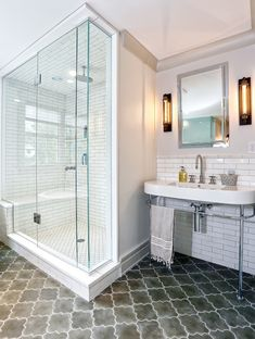 source: DeRosa Builders  Fantastic bathroom features corner walk-in shower accented with white tiles in brick pattern with dark grout next to inset framed medicine cabinet paired with 2-leg oval washstand over gray Moroccan Tiled floor.