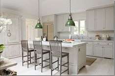 green industrial pendants, grey barstools, white cabinetry, whitewashed wood floors, marble counters