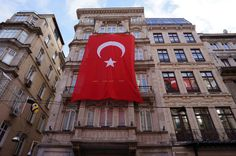 The Turkish flag proudly hangs over a building in Istanbul, Turkey.