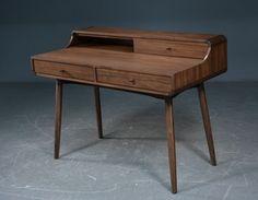 Skrivebord med aflægningshylde i finéret valnød, monteret med runde ben i massiv valnød. Front med 2 skuffer. H. 77/89 cm. L. 120 cm. D. 60 cm. Fremstår delvist samlet i original emballage (kun ben skal monteres). <br><br>Emballage mål: 128x67x37 cm.