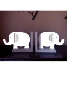 These adorable Elephant bookends are made of wood and measure 8.5 x 7.5. The colors can be changed to match your room decor. The elephants are painted white with a gray and white chevron ear. The bookend bases are painted a stone gray. Great gift idea