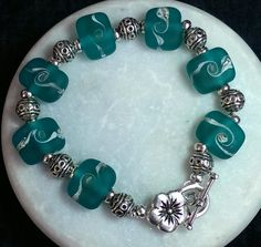 'Jessica' etched teal murano glass nuggets with Tibetan silver beads and. Flower clasp. £22. #destinypier #murano